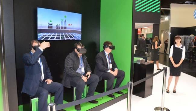 Besucher nutzen auf einem Messestand VR-Brillen mit virtuellen Inhalten