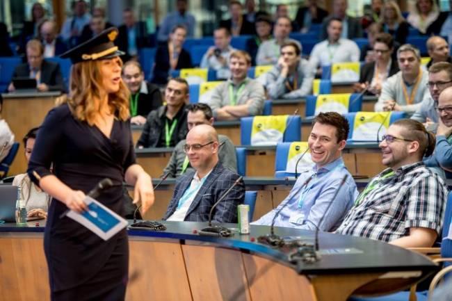 Die Moderatorin begrüßt die Gäste als Pilotin gekleidet.