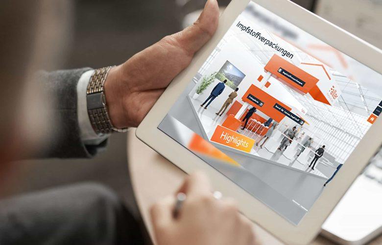 Ein Mann betrachtet auf seinem iPad-Tablet einen interaktiven, digitalen, hybriden Messestand, Entworfen und Realisiert von commacross für Faller Packaging.