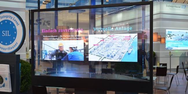 Transparentes Display auf einem Messestand mit moderner Medienbespielung, Inhalte neu praesentiert!