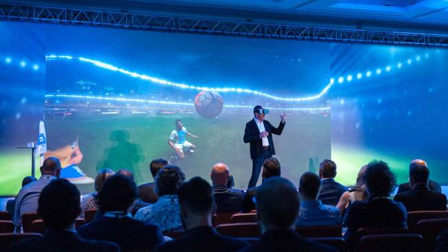 Mann auf großer Buehne vor Publikum mit VR-Brille