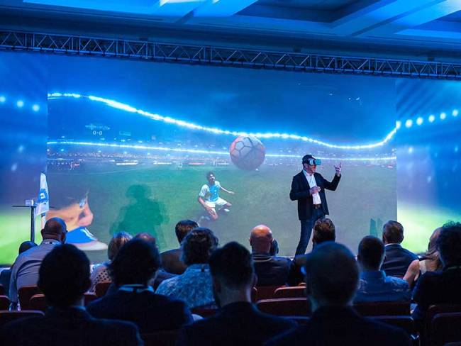 Vorführung einer 3D-Brille vor interessiertem Publikum. Dahinter wird auf einer Leinwand übertragen, was der Träger durch die Brille sieht.