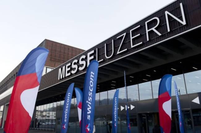 Außenansicht der Messe Luzern mit Swisscom gebrandeten Fahnen davor.
