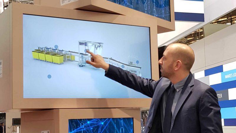Mann toucht auf einem Touchscreen durch eine interaktive Produktpräsentation.